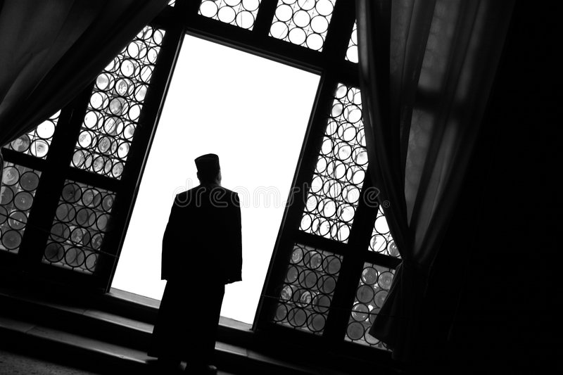 Monk at Window. A Priest/Monk standing at a window in a palace stock photography