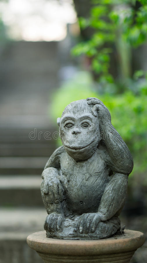Monkey figure. Touching its head, with a tree brush in the background royalty free stock image