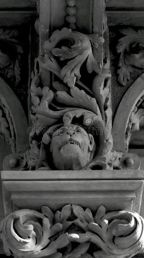 Monkey head under the leaves. Shot in black and white detail on the sculpture on the facade of this historic building representing some characters / animals / royalty free stock photos