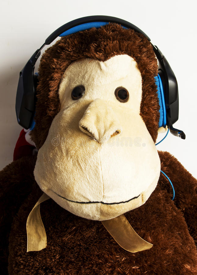 Monkey with headphones. Monkey toy with headphones listening music royalty free stock photos