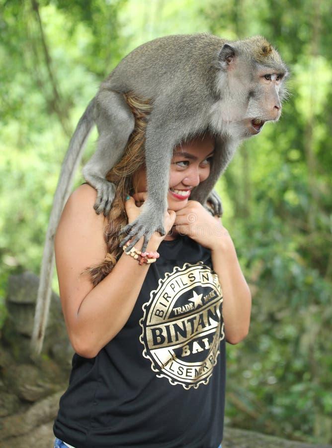 Monkey l'allocation des places sur la tête de touristes dans Forest Sanctuary sacré, Bali photographie stock libre de droits