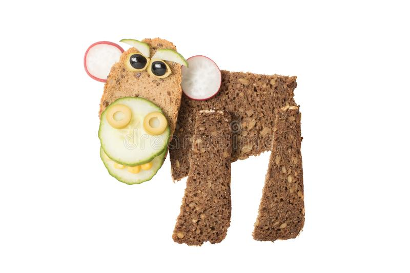 Monkey made with black bread and vegetables. Monkey made with black bread, cucumber, radish, olive and corn. Shot with Canon 760D, ISO 100. Isolated background.n stock photos