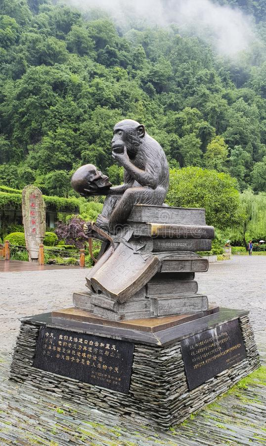 A monkey sitting on books holding a human crane statue at the garden of the Yellow Dragon Cave, Zhangjiajie, Hunan Province, China royalty free stock image
