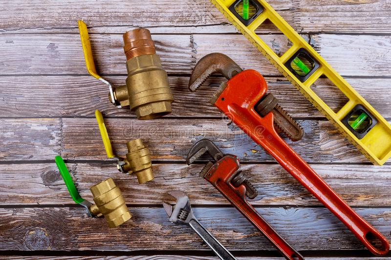 Monkey wrench brass plumbing fittings and level tape on construction concept. Monkey wrench brass plumbing fittings and level tape on gate ball vales royalty free stock images