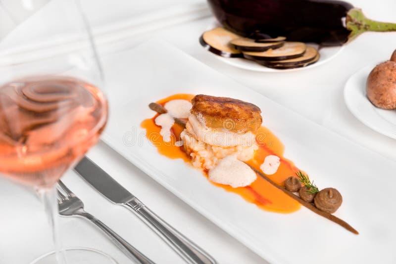 Monkfishfilé med aubergine och tomater royaltyfri fotografi