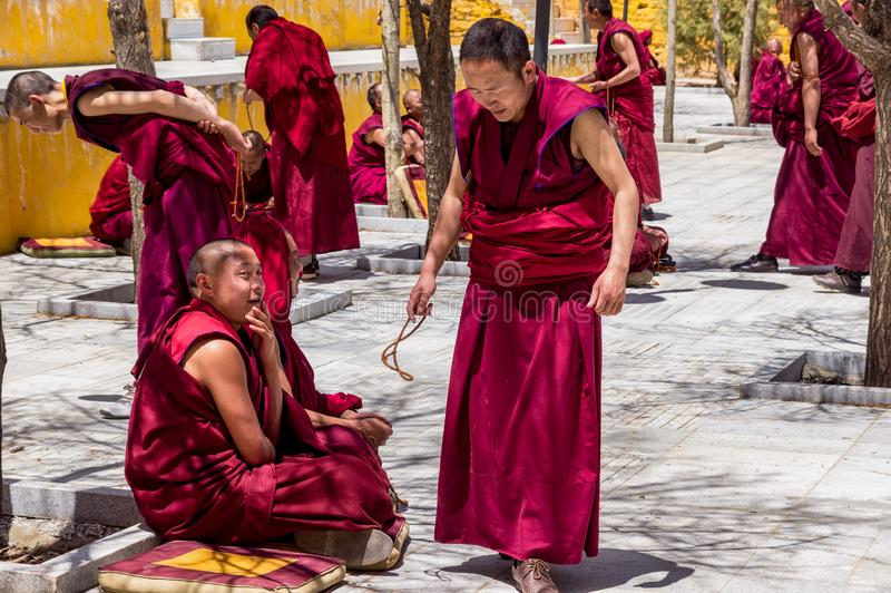 Monks debate at Sera monastery - Tibet. Lhasa, Tibet - April 23, 2012: Tibetan monks at Sera monastery debating in the courtyard royalty free stock photo