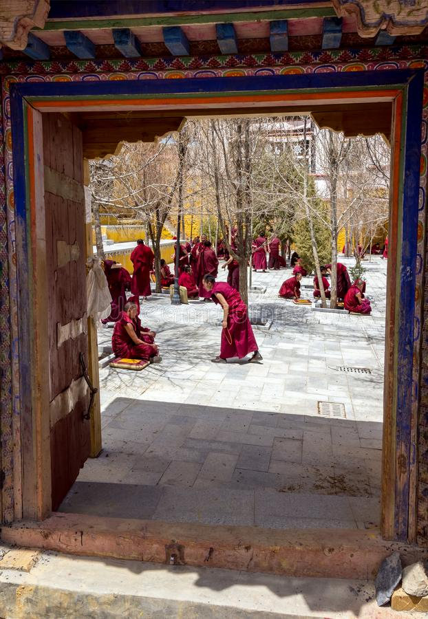 Monks debate at Sera monastery - Tibet. Lhasa, Tibet - April 23, 2012: View through the entrance door of Tibetan monks at Sera monastery debating in the royalty free stock photos