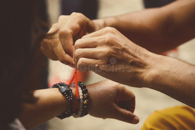 Monks giving blessings for peace & luck. By tie white or red cotton type string around the wrist of people in Cambodia, Laos, Thailand royalty free stock photo