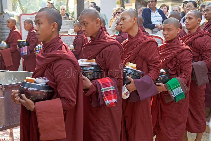 Monks at the Mahagandayon Monastery in Amarapura Myanmar. Buddhist monks in traditional robes make alms in the early morning at the Mahagandayon Monastery in stock photo