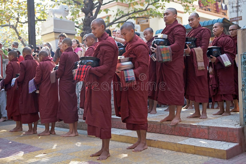 Monks at the Mahagandayon Monastery in Amarapura Myanmar. Buddhist monks in traditional robes make alms in the early morning at the Mahagandayon Monastery in royalty free stock photography