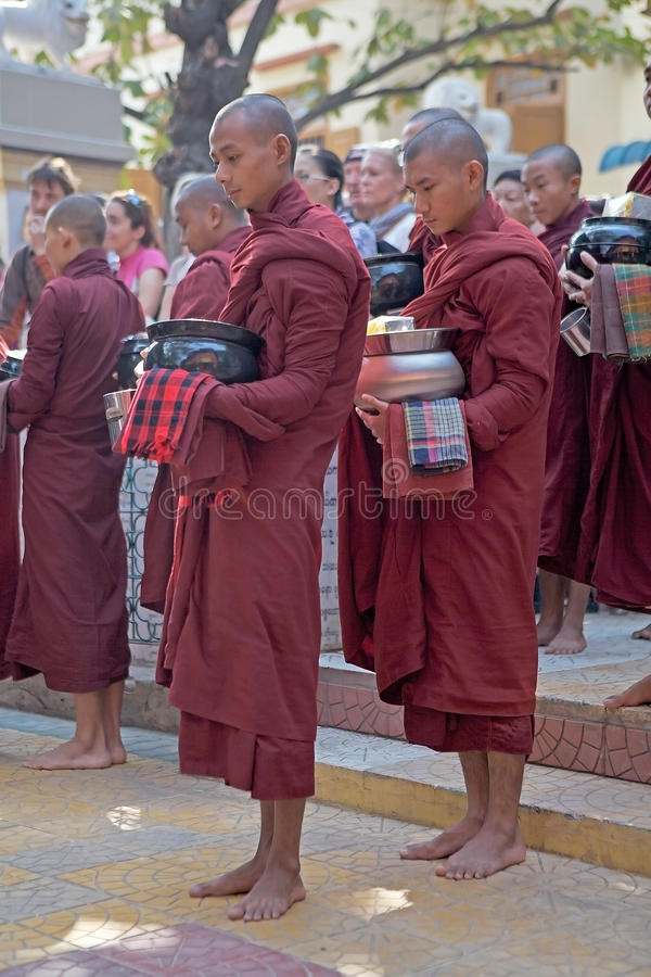 Monks at the Mahagandayon Monastery in Amarapura Myanmar. Buddhist monks in traditional robes make alms in the early morning at the Mahagandayon Monastery in royalty free stock photo