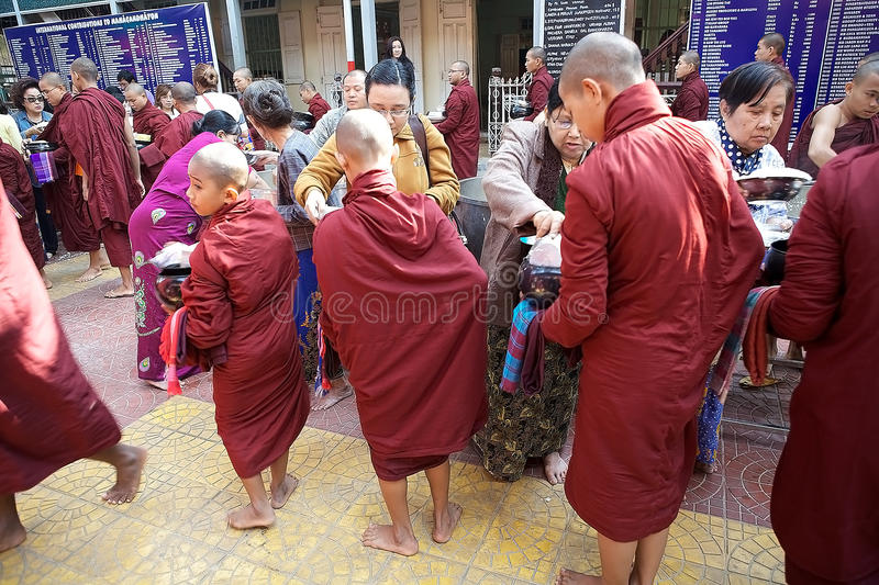 Monks at the Mahagandayon Monastery in Amarapura Myanmar. Buddhist monks in traditional robes make alms in the early morning at the Mahagandayon Monastery in royalty free stock photos
