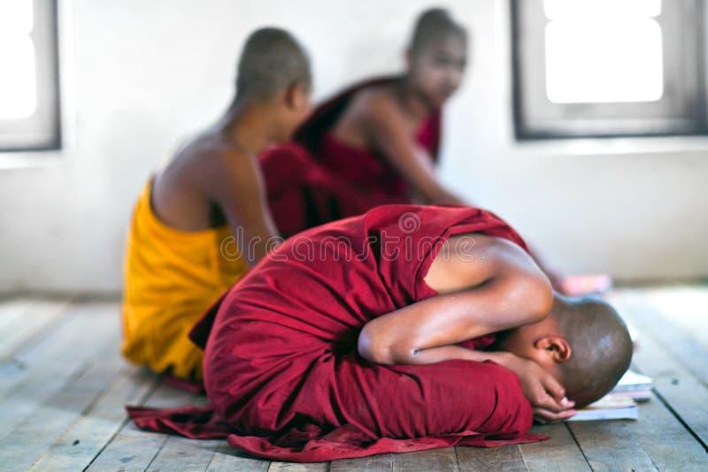 Monks, Myanmar. NYAUNG SHWE, SHAN STATE, MYANMAR - JANUARY 13: Novice monks praying in the Shwe Yan Pyay Monastery on January 13, 2012 in Nyaung Shwe village stock photography