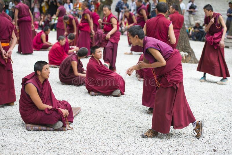 Buddhist monks` debating practice ,one is asking , Sera monastery , Lhasa , Tibet. Monks of Sera monastery practice the debate everyday . monks would debate stock photography