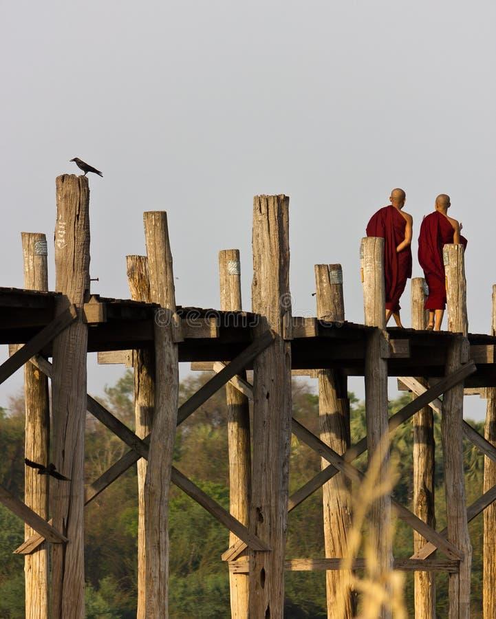 Monks som går på bron för U Bein i Myanmar royaltyfria foton