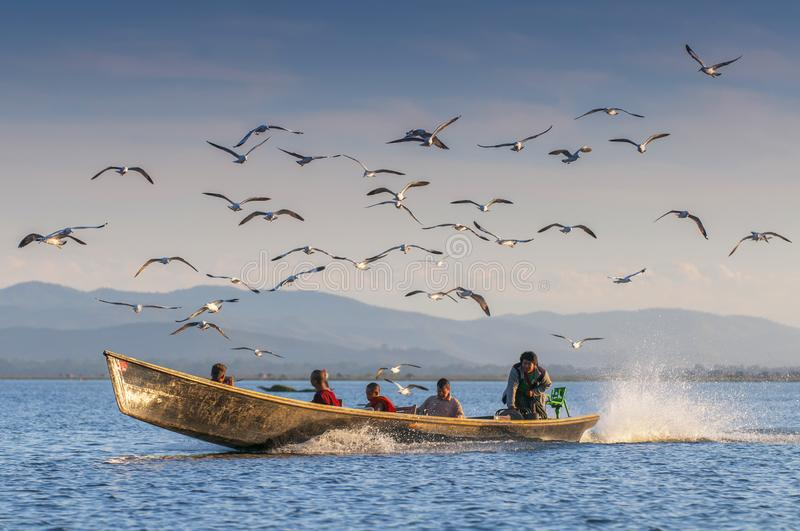 Monks and tourists take a boat trip to Inle lake to visit villages, temples, and floating farm. Taking a boat is a common way to. Enter Inle lake area, Myanmar royalty free stock images