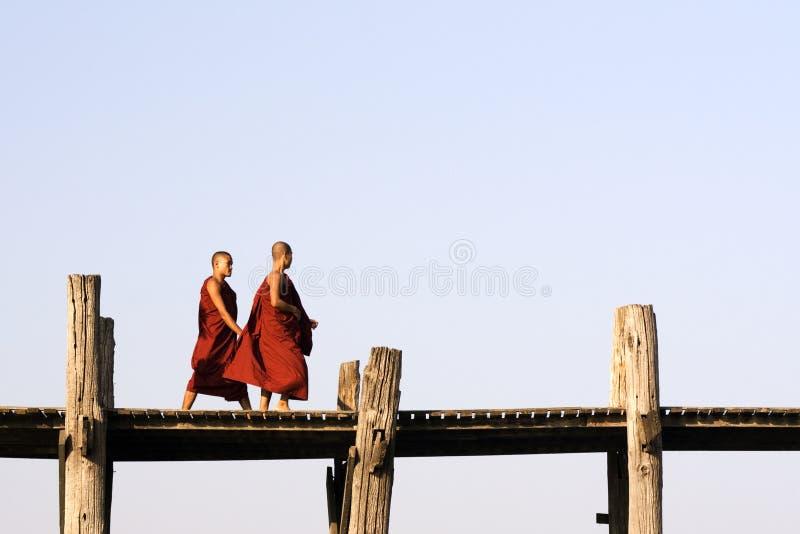 Monks on U Bein bridge in Amarapura, Myanmar (Burma) royalty free stock images