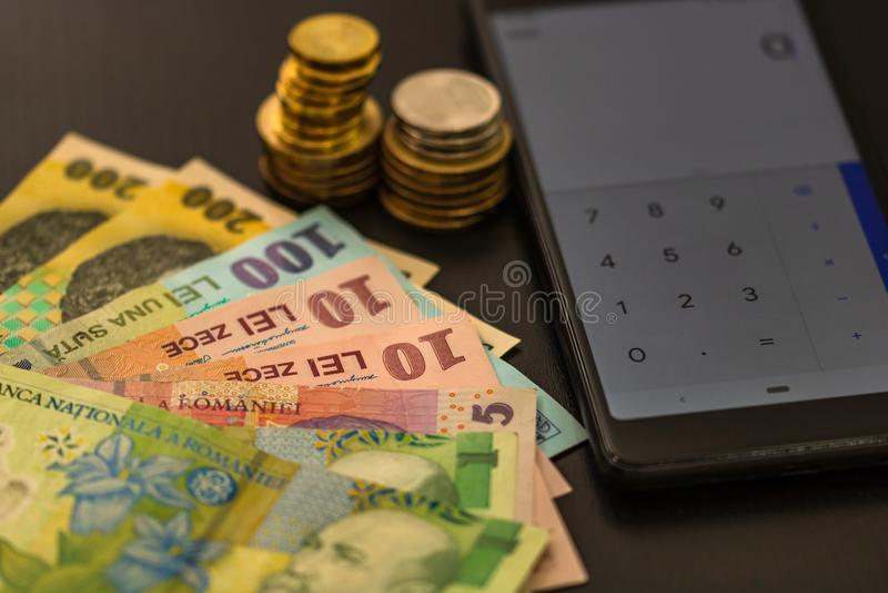 Monnaie roumaine LEI sur fond noir avec calculatrice mobile Argent, impôts, concept d'actualités image libre de droits