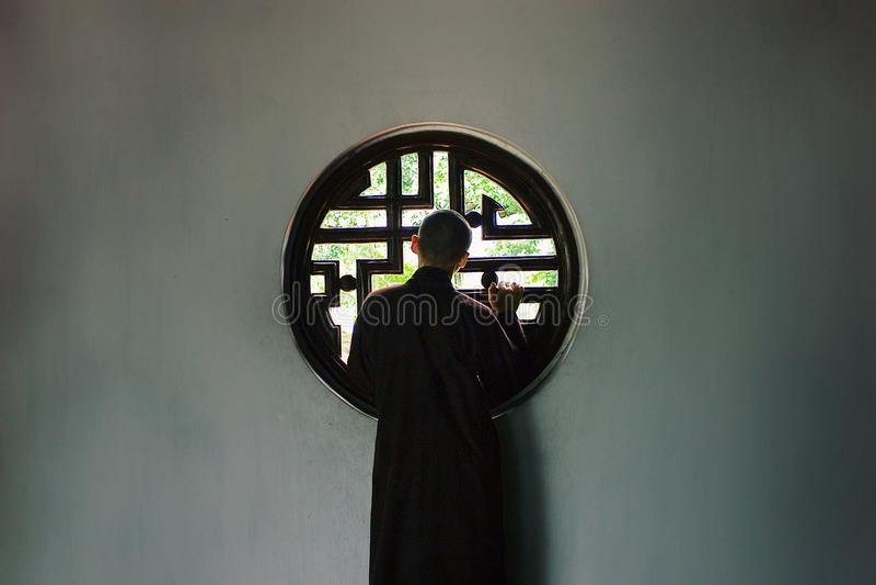 Monnik die buiten van een venster in het minimale iconische plaatsen kijken stock afbeelding