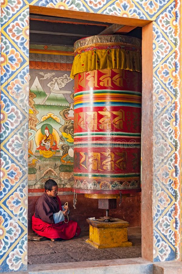Monnik die in een huis van het gebedwiel bidden - Bhutan stock afbeelding
