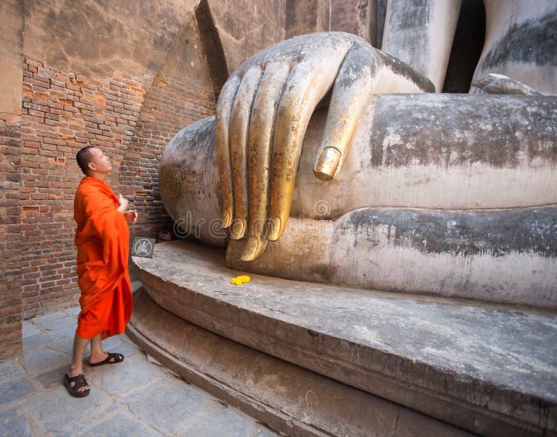 Monnik die voor het Grote Standbeeld van Boedha in Wat Si Chum, het Historische Park van Sukhothai, Thailand bidden stock fotografie