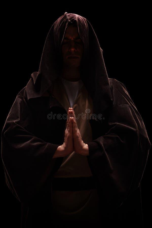 Monnik met een kap bij zijn het hoofd bidden stock afbeelding