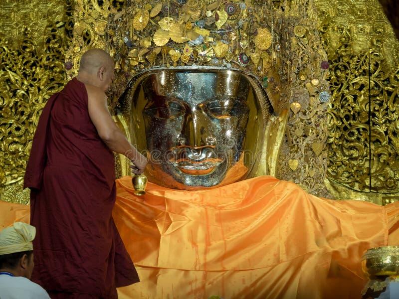Monnik myanmar die het gezicht van Mahamuni Boedha wassen royalty-vrije stock foto