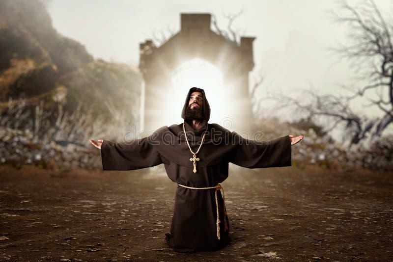 Monnik in zwarte robe met en kap die knielen bidden stock afbeelding