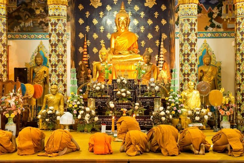 Monniken die in kerk bidden stock foto's