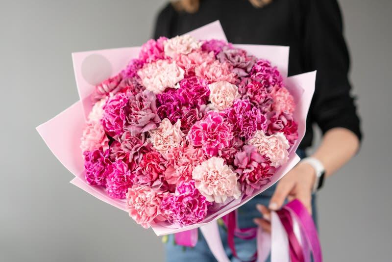 Mono bouquet Um monte de flores de craveiro de cor rosa rica Cama de primavera na mão da mulher Presente para o Dia das Mães fotografia de stock