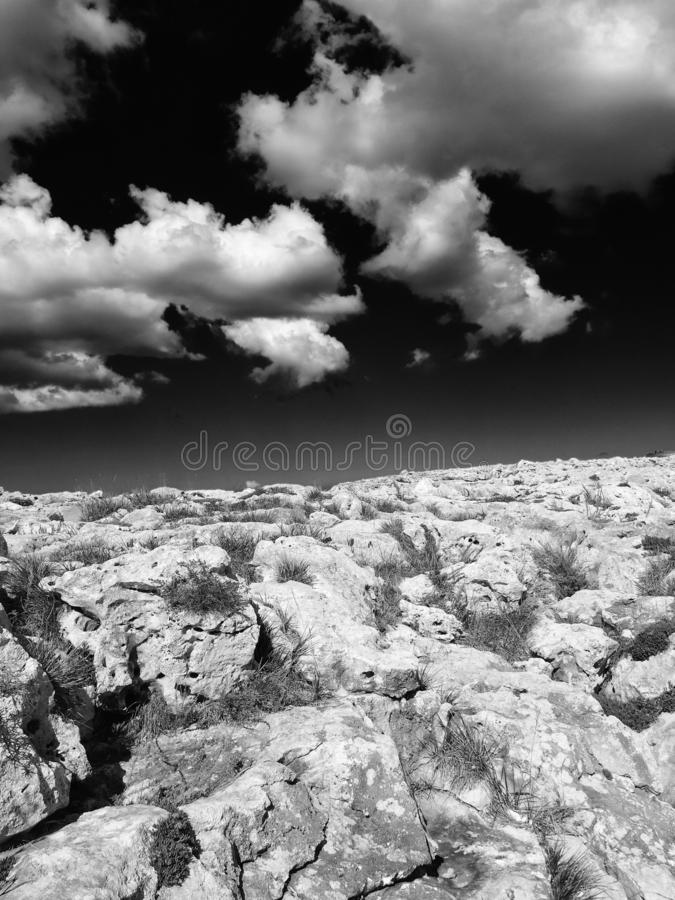 Monochome surreal image of a harsh rocky landscape in bright light with dark contrasting sky and white clouds stock photo