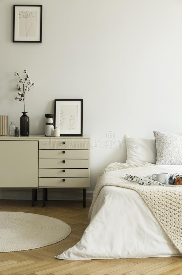 A monochromatic beige and white bedroom interior with a view at a bed and a drawer cabinet standing on a wooden floor. Real photo. Concept stock photos