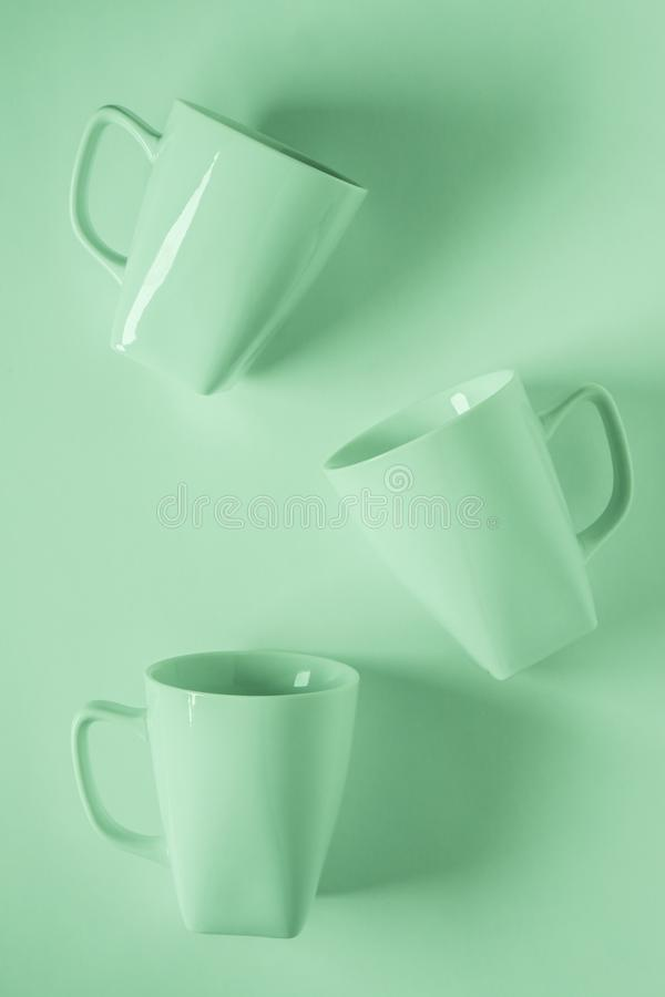 3 Green coffee mugs on green background scattered with empty copyspace stock photos