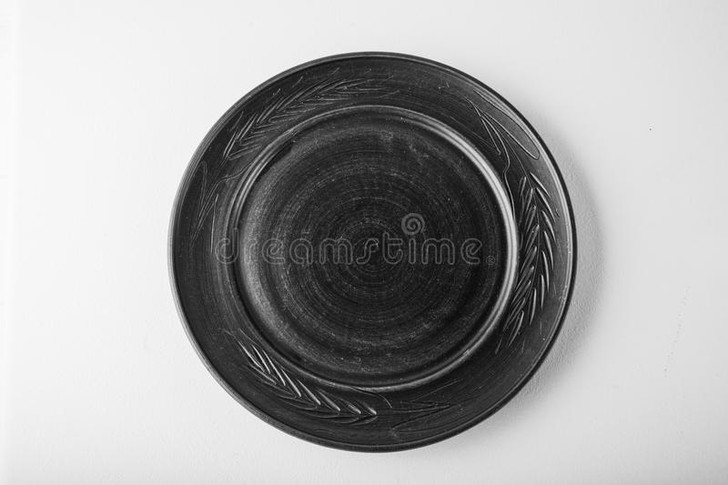 Monochromatic image. Top view of a black pastel plate on a pastel white background. Minimalism food photography. Geometric style. royalty free stock images