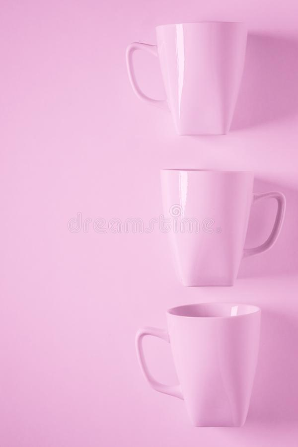 3 pink coffee mugs on pink background in a vertical row with empty copyspace. 3 monochromatic pink coffee mugs lined up in a row on pink background with blank royalty free stock photos