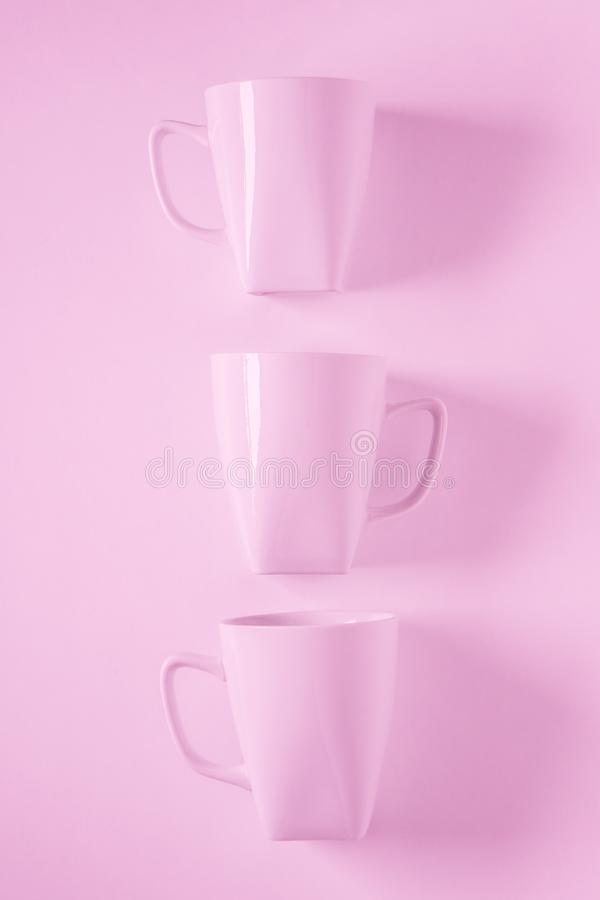 3 pink coffee mugs on pink background in a vertical row with empty copyspace. 3 monochromatic pink coffee mugs lined up in a row on pink background with blank stock photo