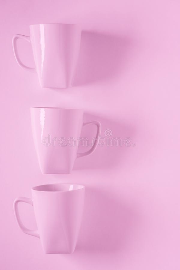 3 pink coffee mugs on pink background in a vertical row with empty copyspace. 3 monochromatic pink coffee mugs lined up in a row on pink background with blank royalty free stock image