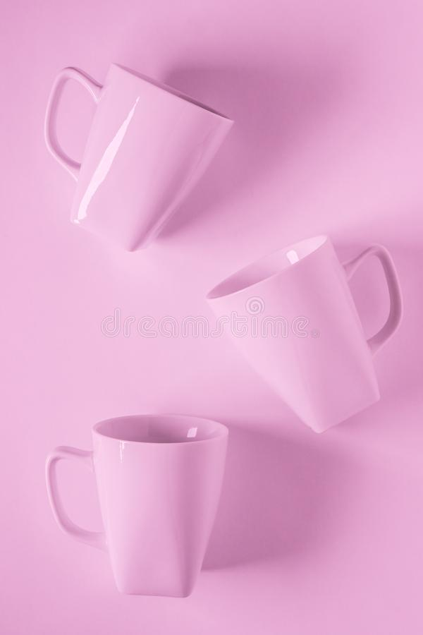 3 pink coffee mugs on pink background scattered with empty copyspace. 3 monochromatic pink coffee mugs scattered on pink background with blank empty room space stock photography