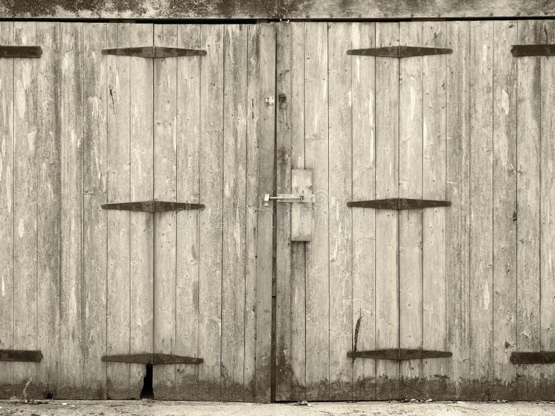 Monochromatyczny stary wiejski siwieje deski deski drewnianych drzwi z sworzniowym uczepieniem i ośniedziały żelazo zależy od obraz royalty free