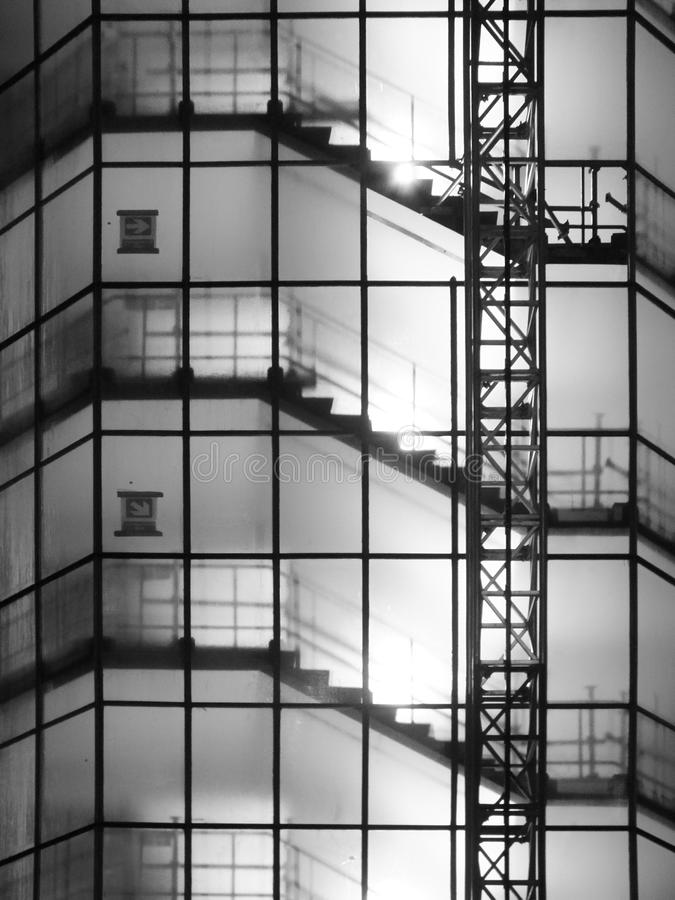 Monochromatyczny wizerunek schody w wysokim wieżowu na budowie przy nocą z basztowym rusztowaniem i dźwignikiem zdjęcia royalty free