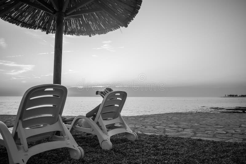 Monochrome изображение тропического пляжа на заходе солнца как женщина ослабляет стоковая фотография rf