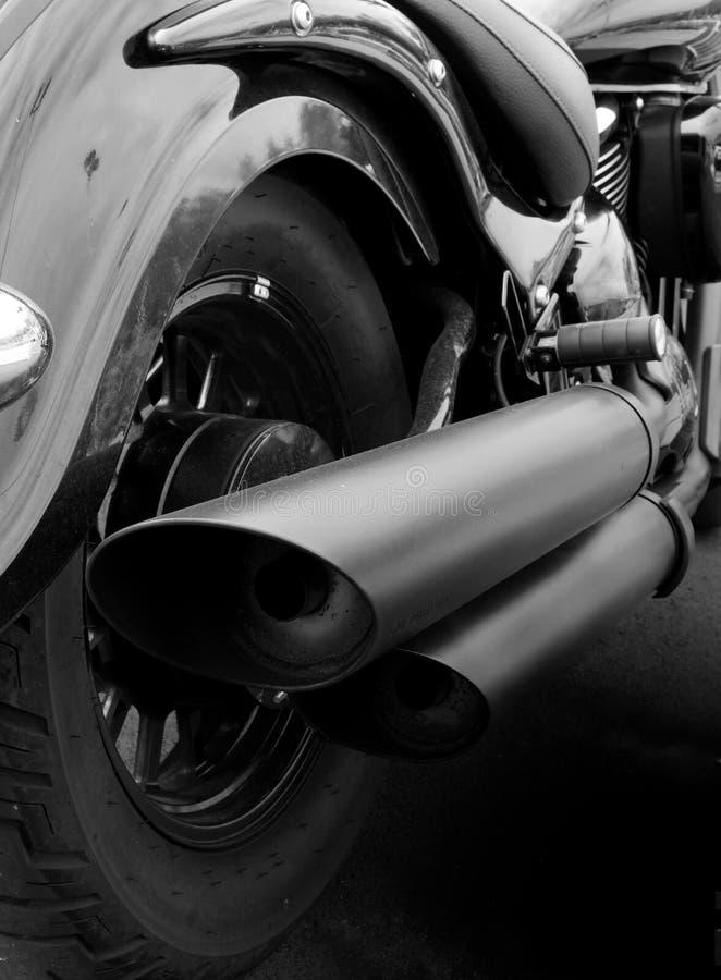 Monochrome конец вверх задней части винтажного мотоцикла с mudguard заднего колеса и широкими выхлопными трубами стоковая фотография
