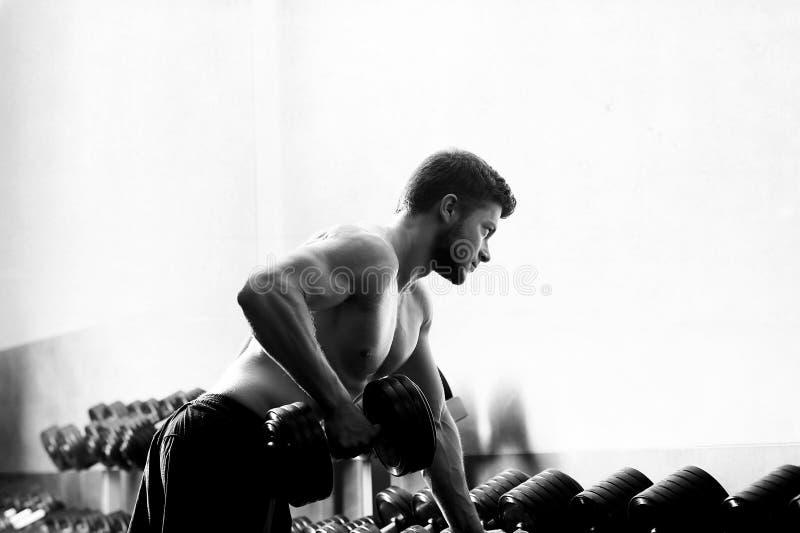 Monochrome съемка сорванного без рубашки человека работая с dumbbe стоковая фотография rf