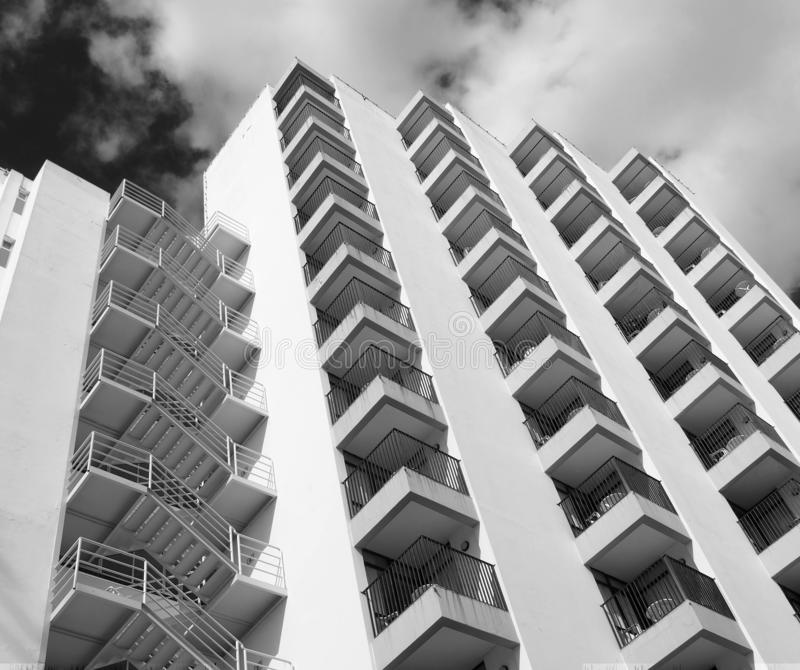 Monochrome angled detail view of an old 1960s white concrete apartment building with steps and balconies against sky and clouds royalty free stock photography
