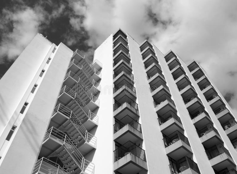 Monochrome angled detail view of an old 1960s white concrete apartment building with steps and balconies against sky and clouds royalty free stock images
