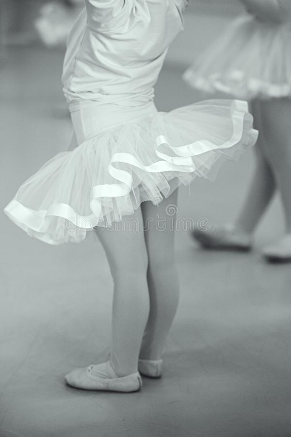 Monochrome - baby ballet students in little pink tutu with pink satin ribbon, leotard and ballet wrap stock photography