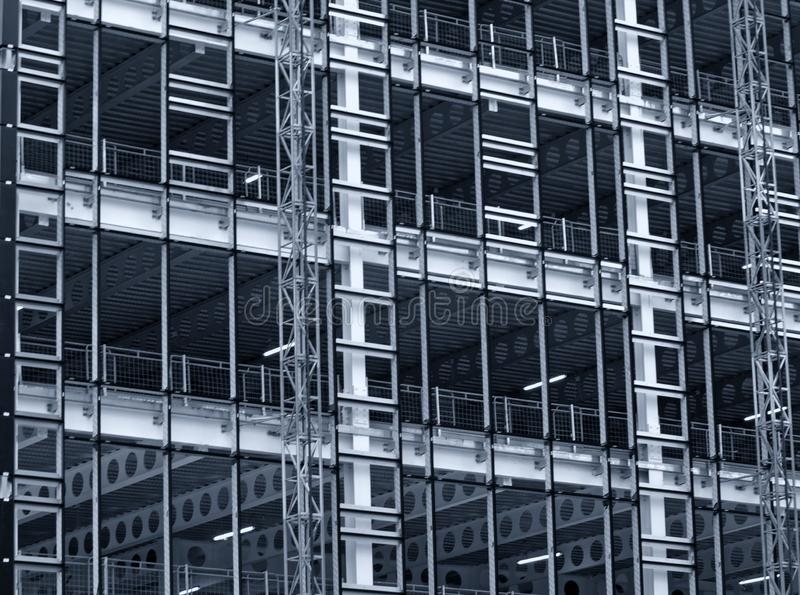 Monochrome blue tinted view of a large building development under construction with steel framework and girders royalty free stock photo