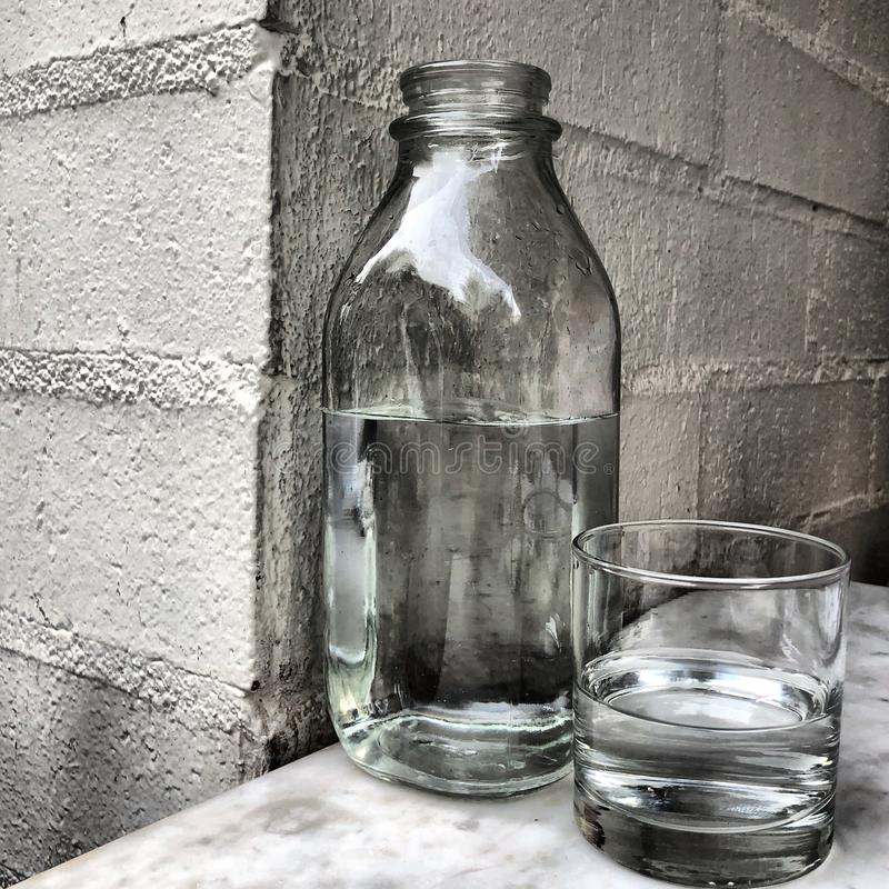 Bottle and glass of water stock images