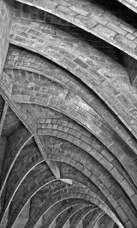 Monochrome close up of old repeating underground pointed brick arches. A monochrome close up of old repeating underground pointed brick arches royalty free stock photo
