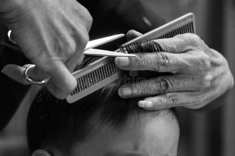 Monochrome closeup hands of barber holds scissors and comb while cutting the hair of little boy stock photo